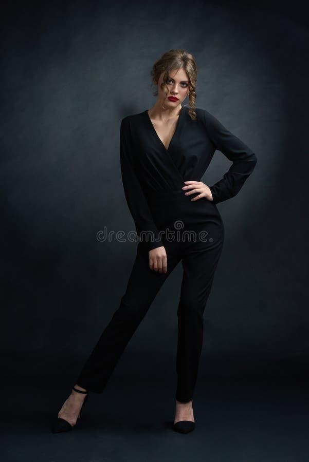 Studio frontview van zekere vrouw die zwart kostuum dragen stock afbeeldingen