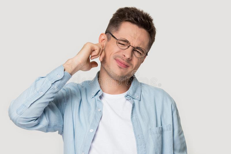 Studio headshot young man suffers from earache or noise stock photos