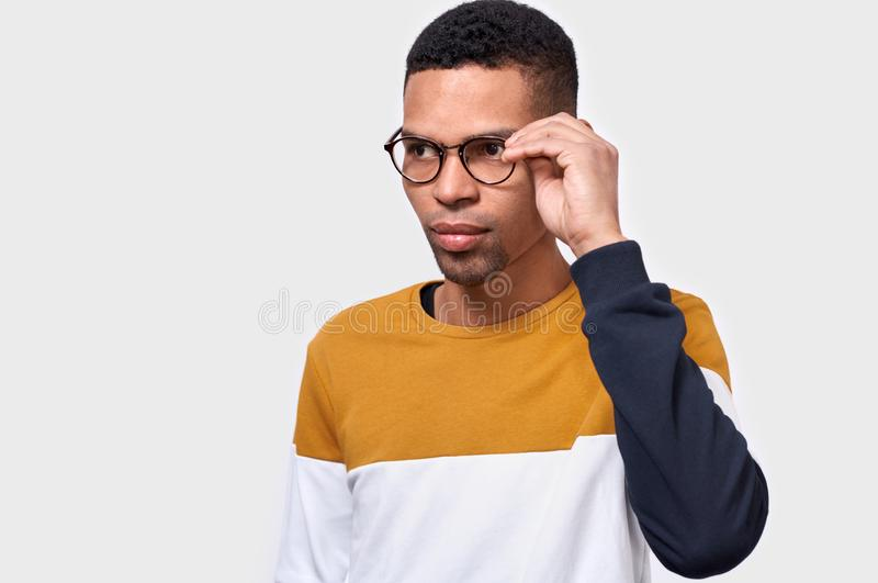 Studio horizontal portrait of serious young African American man wearing and looking through round trendy spectacles. stock photo