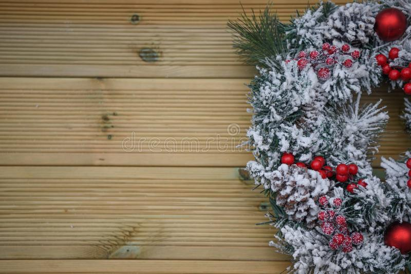Winter christmas photography image of a wreath covered in snow with red berries on a natural wood background royalty free stock photos