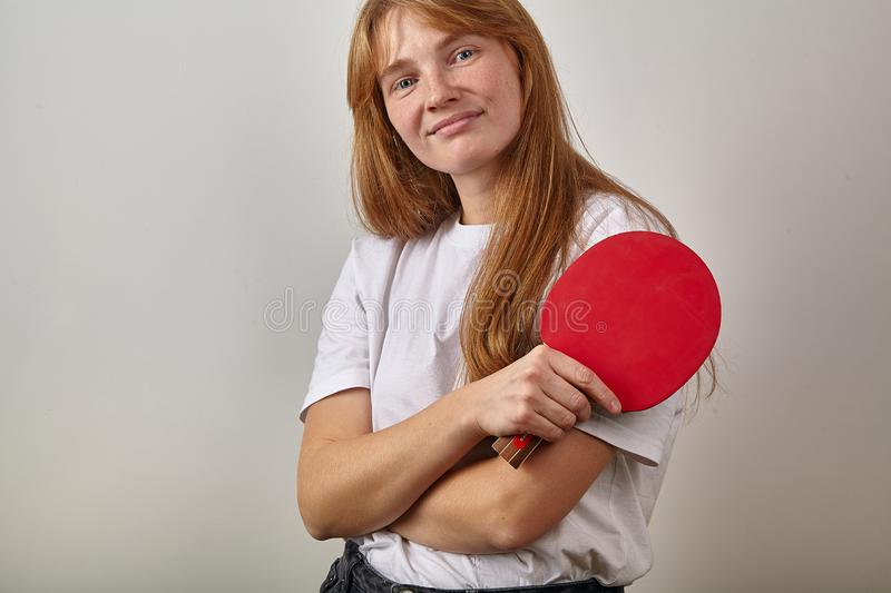 Portrait of young girl with red hair and freckles dressed in white t-shirt holding table tennis racket royalty free stock photography
