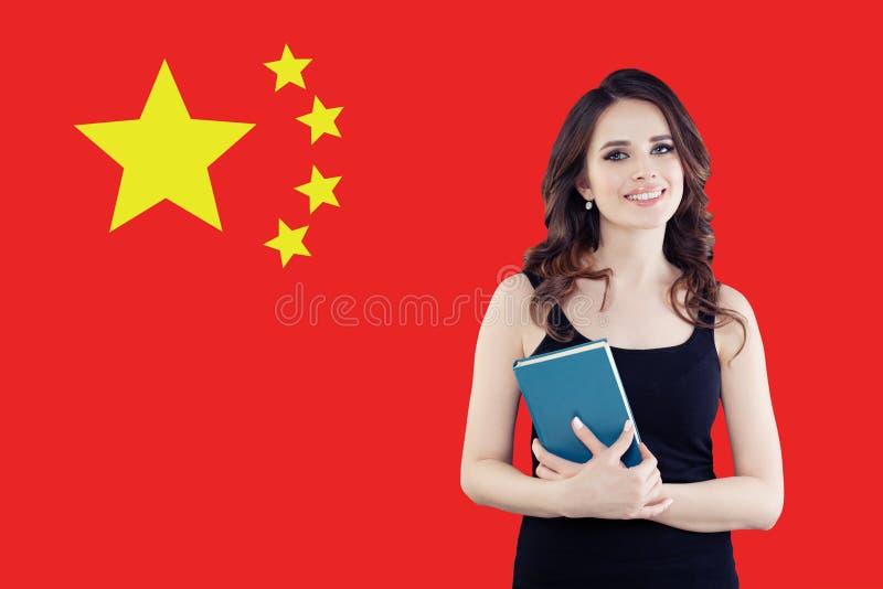 Studio, internato e lavoro nel concetto della Cina Bella donna astuta che sorride sul fondo cinese della bandiera immagini stock libere da diritti