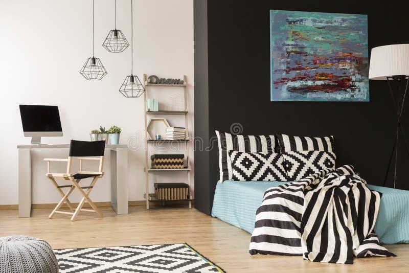 Studio met een slordig bed stock afbeelding