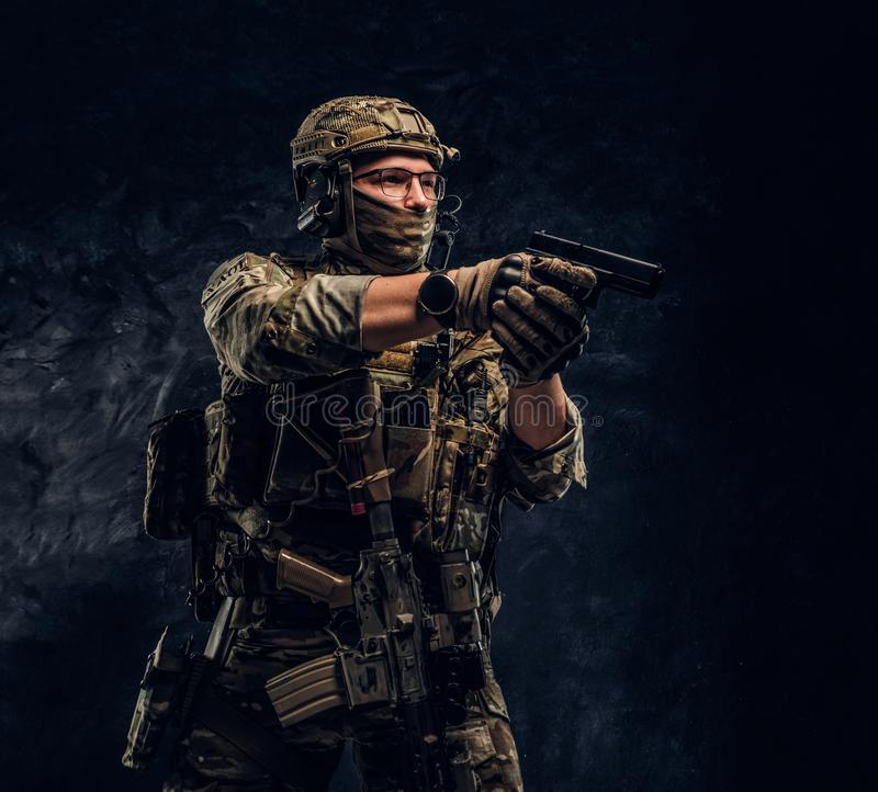 The elite unit, special forces soldier in camouflage uniform holding a pistol and looking sideways royalty free stock image