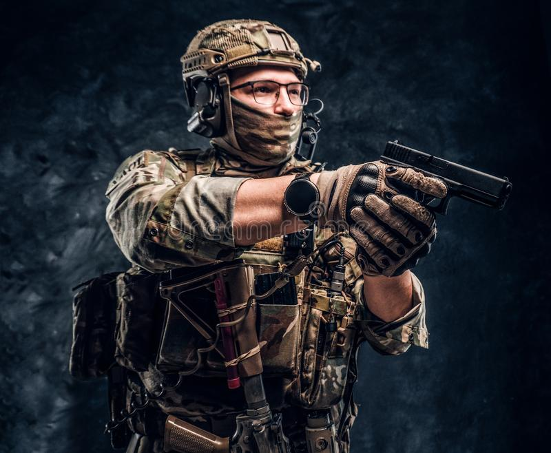 The elite unit, special forces soldier in camouflage uniform holding a pistol and looking sideways. Studio photo against a dark textured wall. The elite unit stock photos