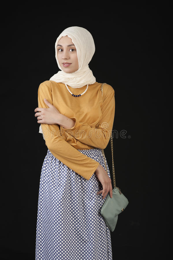 Studio photo eastern girl in a headscarf and a modern Islamic Clothes on a dark background stock image