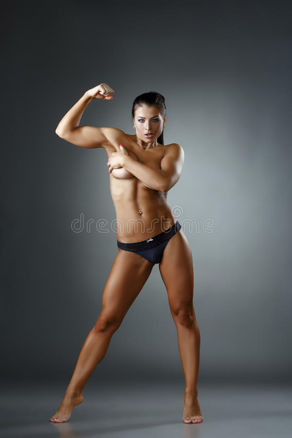 Studio photo of muscular woman showing biceps. Studio photo of female bodybuilder showing biceps royalty free stock images