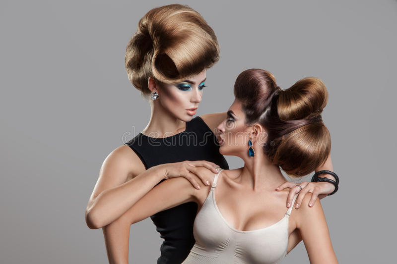 Studio photo of two beauty women with creative hairstyle looking stock image