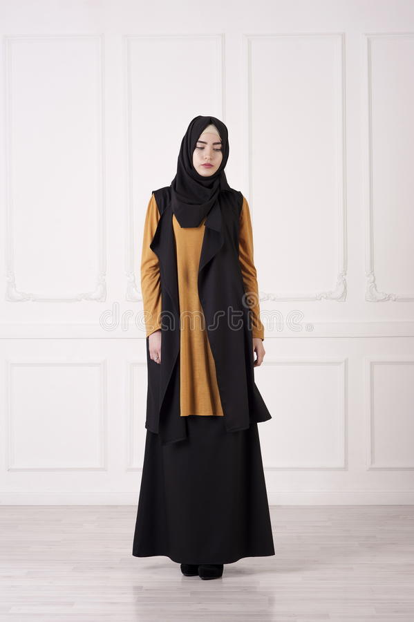 Studio photo of a young woman Caucasian looks in the modern Muslim clothing, a scarf on the head, high heels, on a bright royalty free stock images