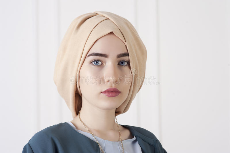 Studio photo of a young woman eastern type in the modern Muslim clothes and beautiful headdress royalty free stock photo
