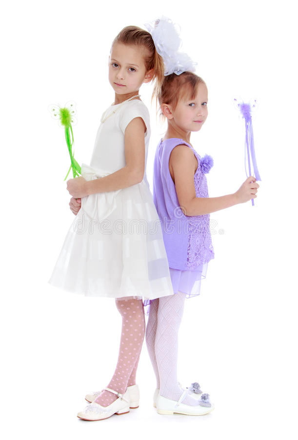 Studio photography of a little girl. Two sisters are each other back and holding a magic wand.Studio photo, isolated on white background royalty free stock photos