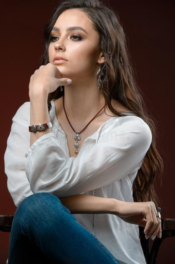 Studio photography. Portrait of a beautiful brunette Model with silver jewelry collection and long hair royalty free stock photos