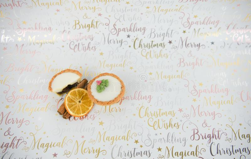Christmas food photography mince pies cinnamon sticks and orange slice on xmas wrapping paper background. Studio photography set up with Christmas food and royalty free stock image