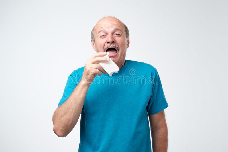 Studio picture of senior man with handkerchief. Sick guy isolated has runny nose. stock photo