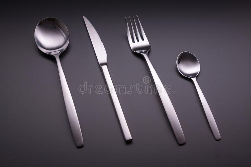 Shiny cutlery over a black background stock images
