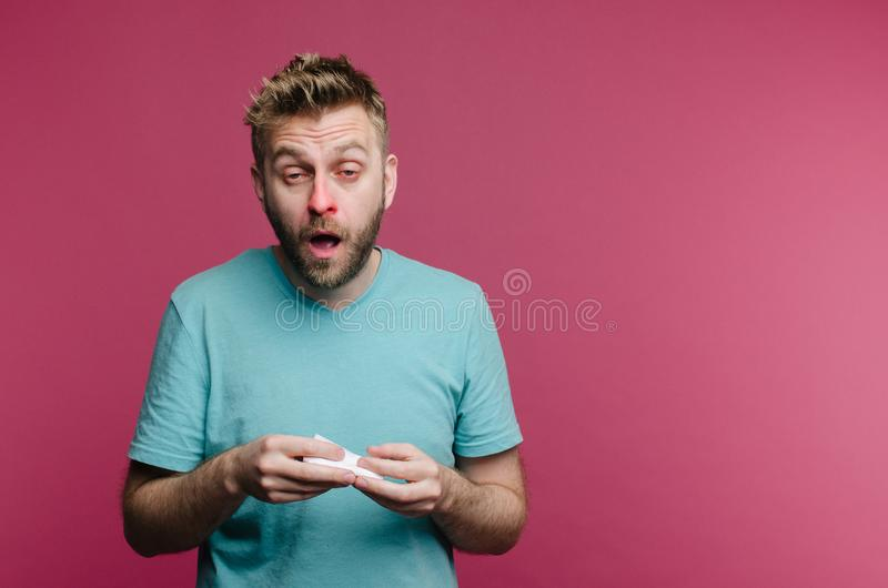 Studio picture from a young man with handkerchief going to sneeze. Sick guy isolated has runny nose. man makes a cure for the. Common cold from the air royalty free stock photo
