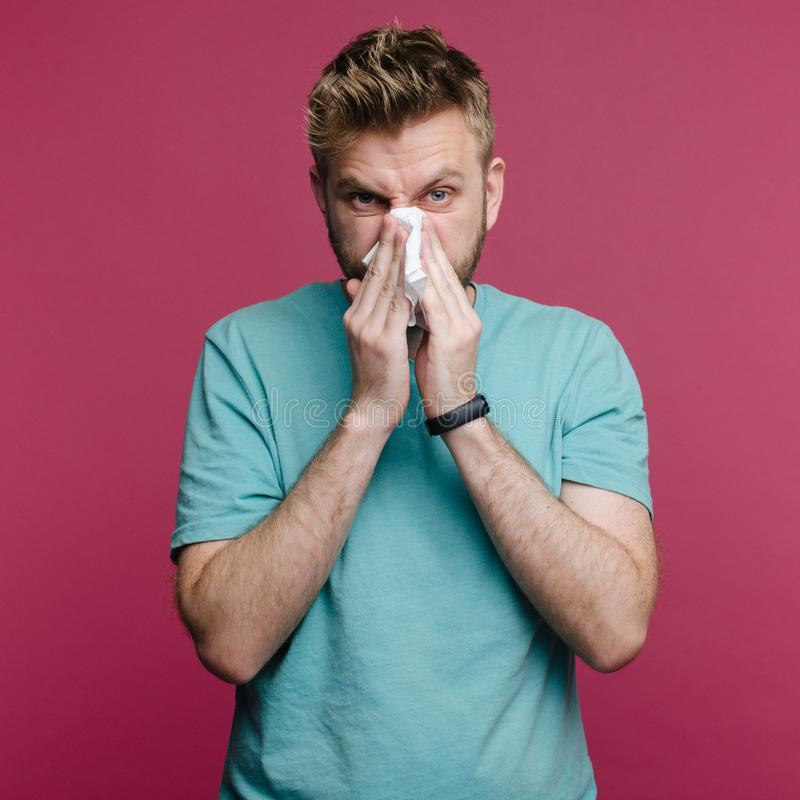 studio picture from a young man with handkerchief. Sick guy isolated has runny nose. royalty free stock images