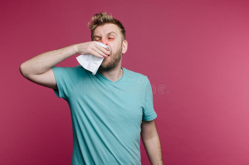 Studio picture from a young man with handkerchief. Sick guy isolated has runny nose. man makes a cure for the common cold royalty free stock photo