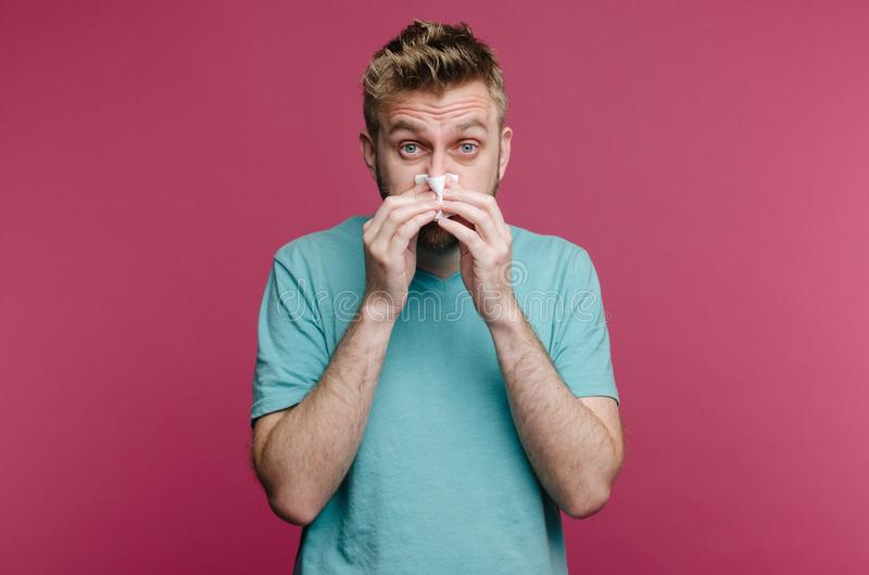 Studio picture from a young man with handkerchief. Sick guy isolated has runny nose. man makes a cure for the common cold royalty free stock images