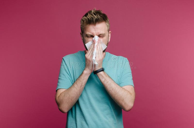 Studio picture from a young man with handkerchief. Sick guy isolated has runny nose. man makes a cure for the common cold. Image stock photography