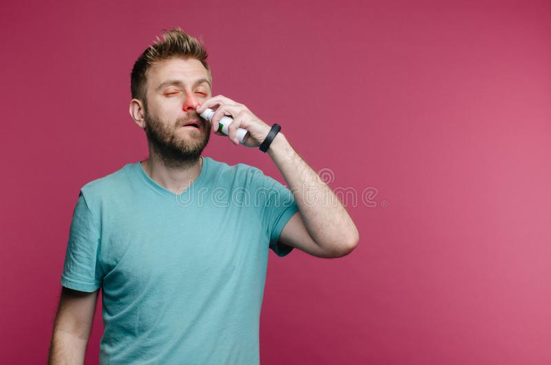Studio picture from a young man uses nose spray. Sick guy isolated has runny nose. man makes a cure for the common cold royalty free stock photos