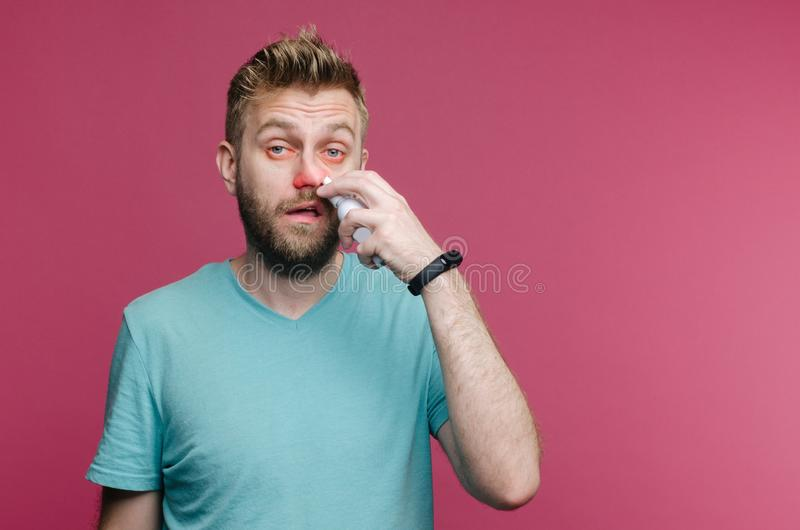 Studio picture from a young man uses nose spray. Sick guy isolated has runny nose. man makes a cure for the common cold royalty free stock photography