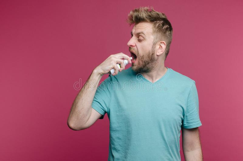 Studio picture from a young man uses spray in the throat. Sick guy isolated has runny nose. man makes a cure for the common cold royalty free stock photography