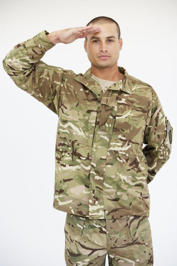 Studio-Porträt von Soldat-Wearing Uniform And-Begrüßung lizenzfreies stockbild