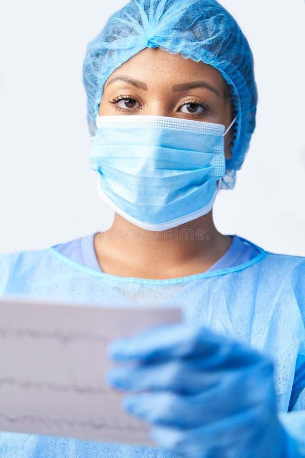 Studio-Porträt weiblicher Chirurg-Wearing Gown And-Maske, die heraus medizinischen Druck hält lizenzfreie stockfotografie