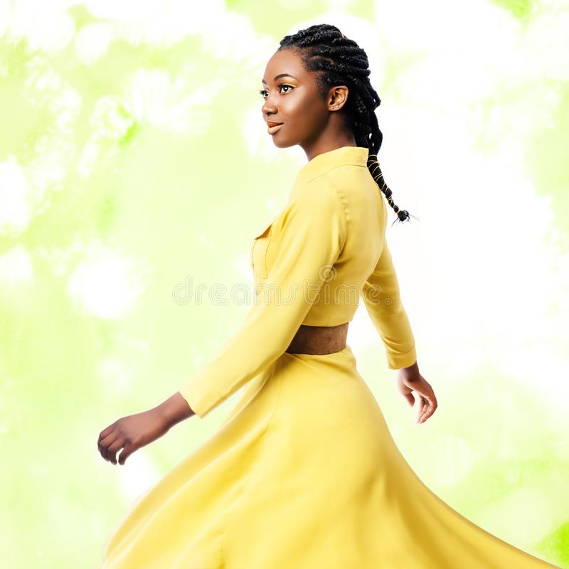 Studio portrait of African woman in yellow dress. Close up studio portrait of young attractive african woman in yellow dress.Girl with braided hairstyle swaying stock images