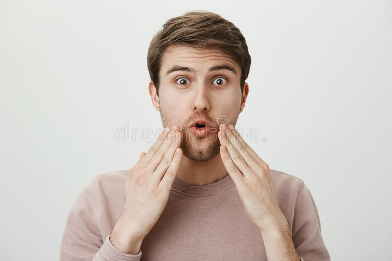 Studio portrait of amazed young man with bristle touching his face with surprised expression, standing against gray. Background. Man shaved long beard and have royalty free stock images