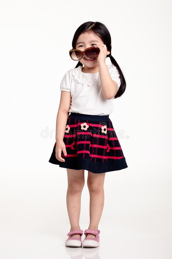 Studio portrait of asian girl child wearing sunglasses and having a bright look stock photos