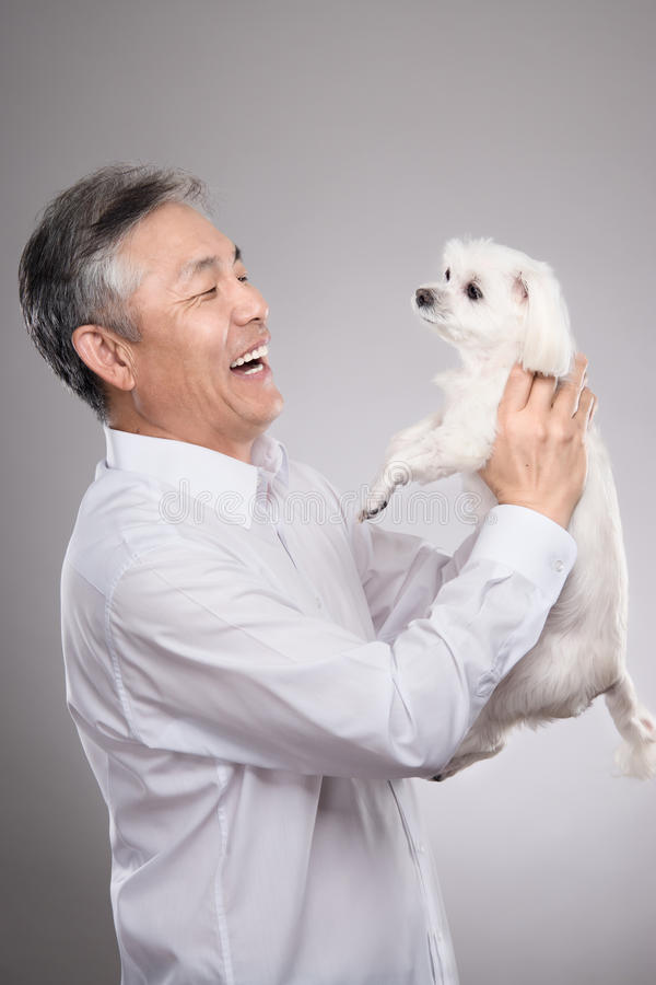 Download Studio Portrait Of Asian Middle-aged Male With Dog Stock Photo - Image: 83724886