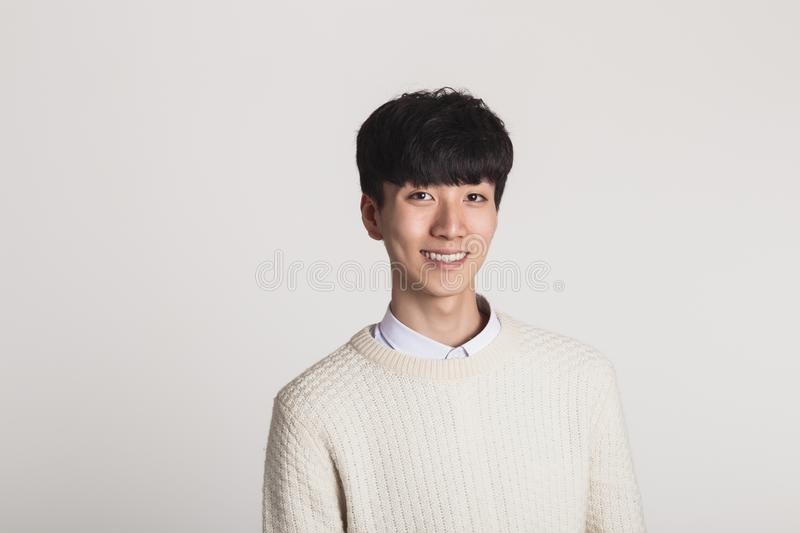 A studio portrait of an Asian young man looking for a camera with confident smiles stock photos