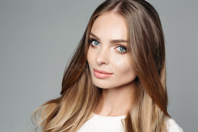 Studio portrait of an attractive blond woman with long thick hair and low-key makeup, wearing an elegant white blouse royalty free stock photo