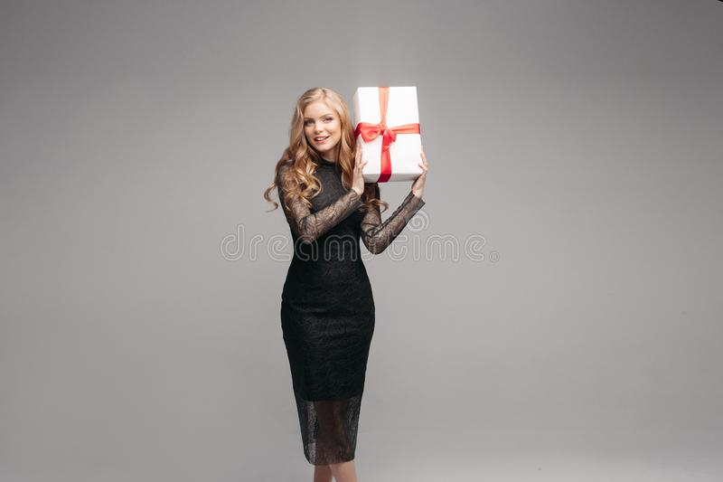 Stunning woman in elegant black dress with Christmas gift. Studio portrait of attractive blonde woman with wavy hair wearing elegant laced black dress holding stock images