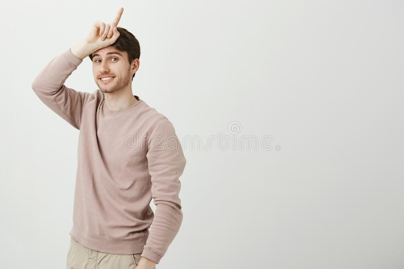 Studio portrait of attractive european man with charming smile holding number one sign near forehead and standing half. Turned over gray background. Sportsman stock photography