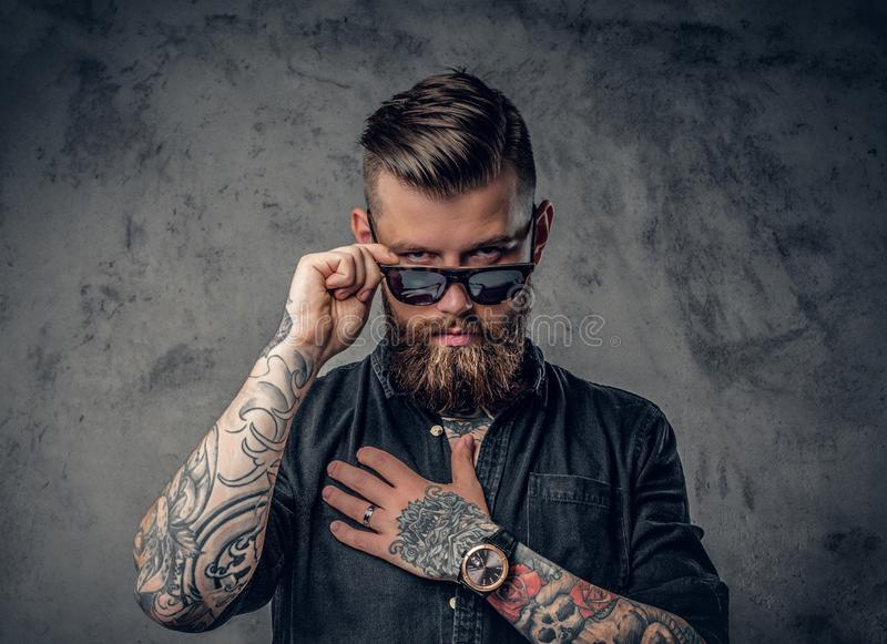 A man with tatoos on his arms. Studio portrait of a bearded hipster man with tattoos on his arms and neck dressed in a black shirt and sunglasses stock image
