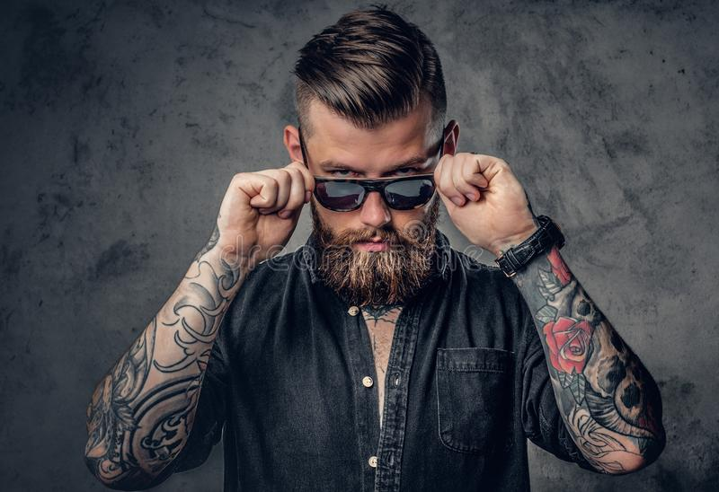 A man with tatoos on his arms. Studio portrait of a bearded hipster man with tattoos on his arms and neck dressed in a black shirt and sunglasses royalty free stock image