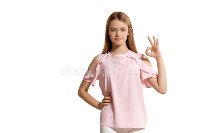 Studio portrait of a beautiful girl blonde teenager in a pink t-shirt posing isolated on white background. stock images