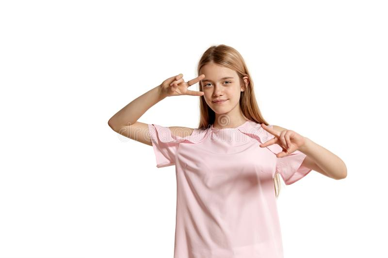 Studio portrait of a beautiful girl blonde teenager in a pink t-shirt posing isolated on white background. stock photo