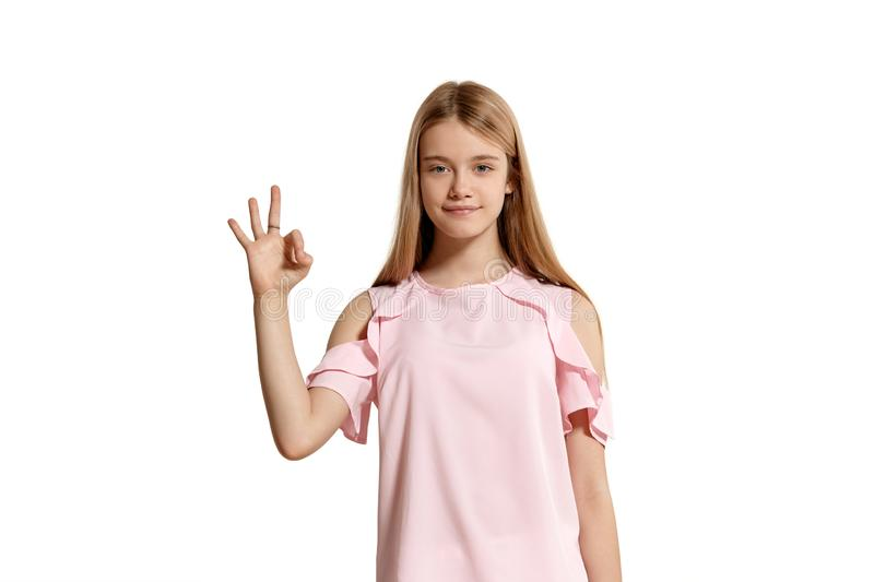 Studio portrait of a beautiful girl blonde teenager in a pink t-shirt posing isolated on white background. royalty free stock image