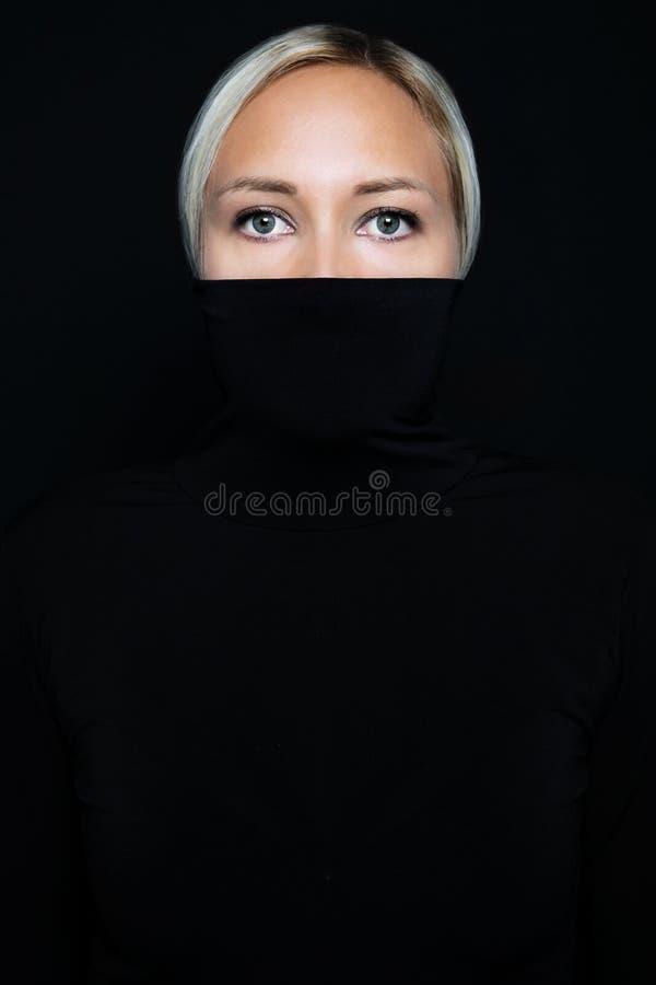 Studio portrait of beautiful elegant woman hiding face in black turtleneck stock photos