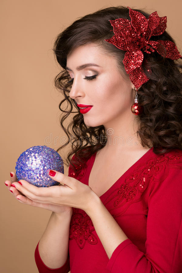 Studio portrait of a beautiful girl with blue Christmas ball in the hands of. Studio portrait of a beautiful girl with red lipstick and blue Christmas ball in royalty free stock photo