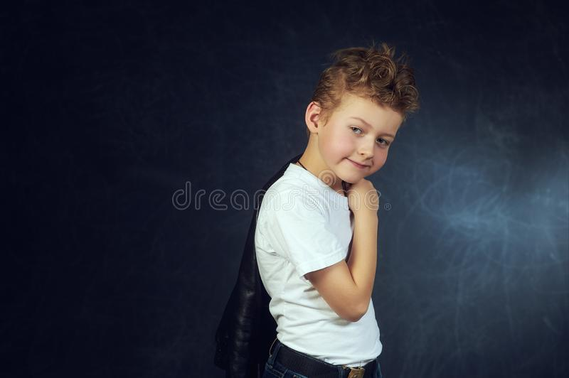 Studio portrait of a beautiful little boy on a dark background royalty free stock photo