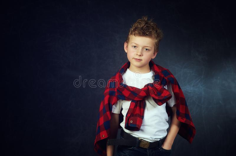 Studio portrait of a beautiful little boy on a dark background royalty free stock photos