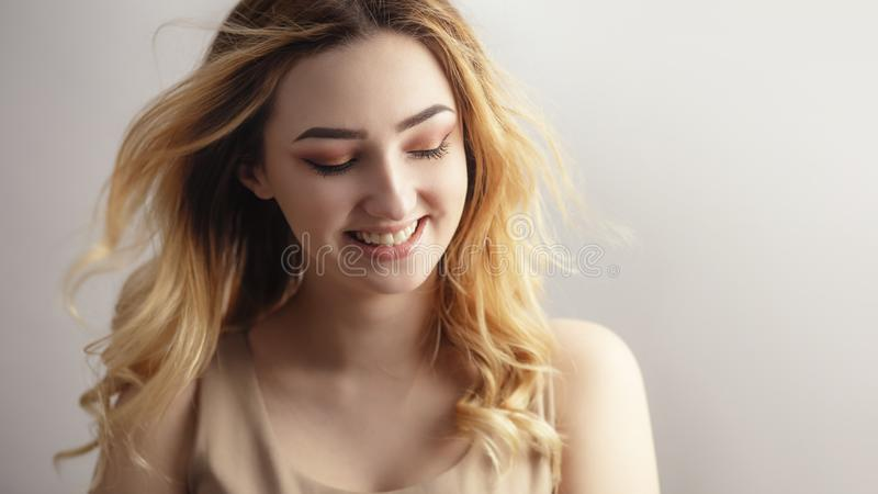 Studio portrait of a beautiful sincerely laughing girl, young woman face with curly hair disheveled from wind , the concept of. Soft studio portrait of a royalty free stock photography