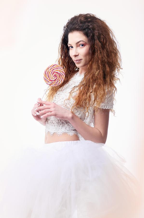 Studio portrait of beautiful smiling young girl with lollipop in hands stock photos