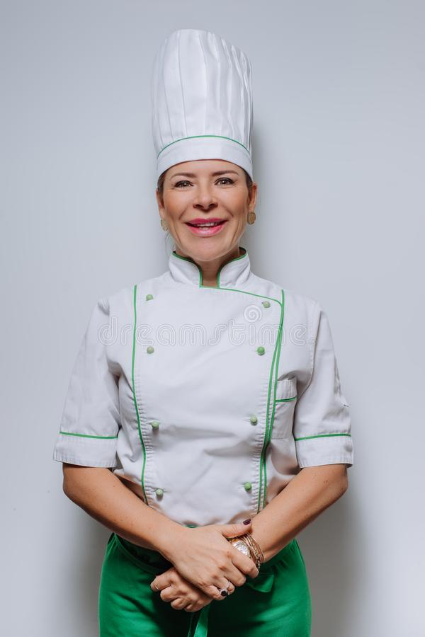 Studio portrait of a beautiful woman chef in uniform. A smiling woman cook in a cap and uniform on a gray background. royalty free stock images
