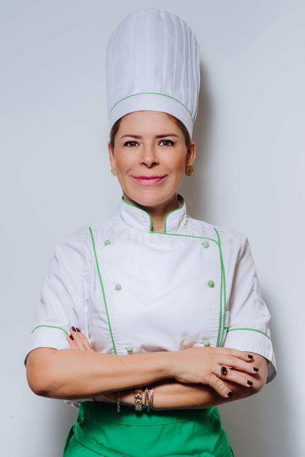 Studio portrait of a beautiful woman chef in uniform. A smiling woman cook in a cap and uniform on a gray background. royalty free stock photos